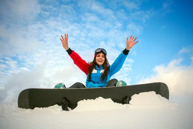 Snowboarder alegre mulher sentada no topo da montanha no céu azul