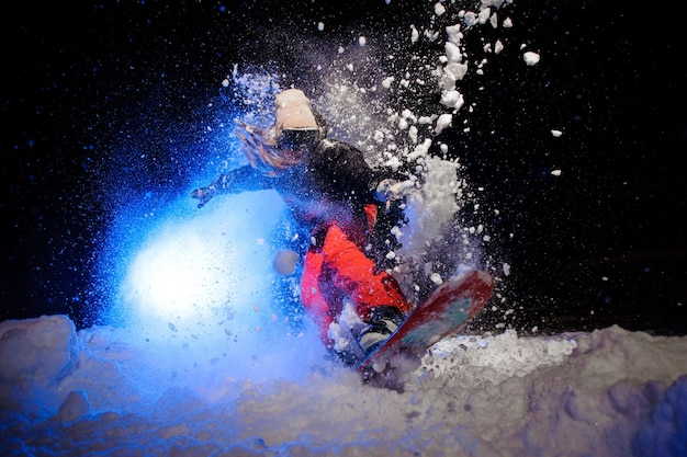 Snowboarder ativa vestida com uma roupa esportiva laranja, pulando na encosta da montanha à noite sob a luz azul
