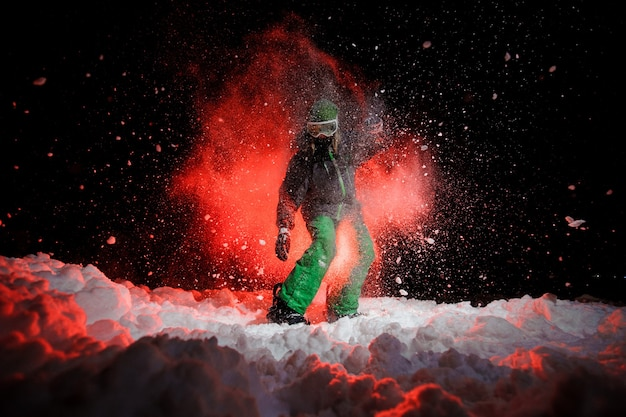 Snowboarder ativa vestida com uma roupa esportiva verde em pé sob a neve durante a noite sob a luz vermelha
