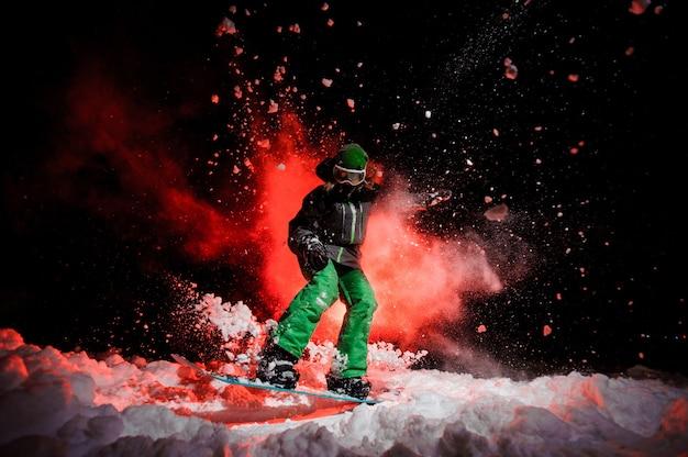 Snowboarder ativa vestida com uma roupa esportiva verde, pulando sob a neve durante a noite sob a luz vermelha