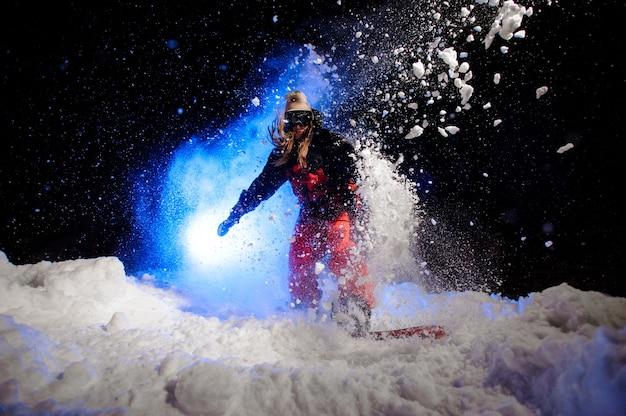 Snowboarder ativa vestida com uma roupa esportiva vermelha, pulando na encosta da montanha na neve durante a noite sob a luz azul