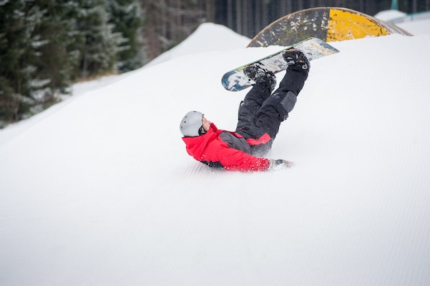 Snowboarder cai para avaliar nas encostas durante a descida