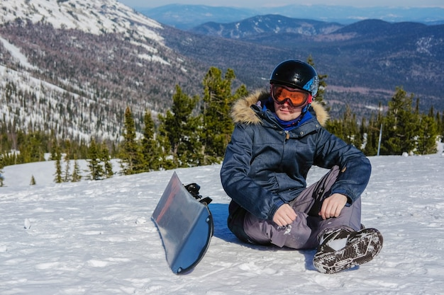 Snowboarder com capacete e máscara de óculos sentado no topo de montanhas