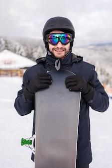 Snowboarder de homem fica com snowboard. retrato do close up.