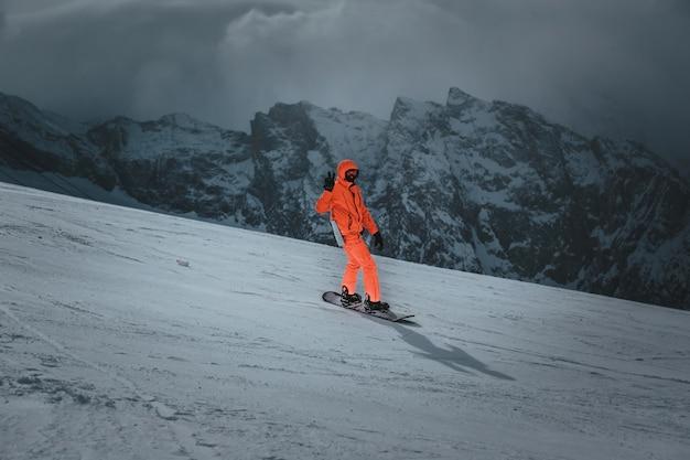 Snowboarder de homem passeios na encosta. estância de esqui. espaço para texto