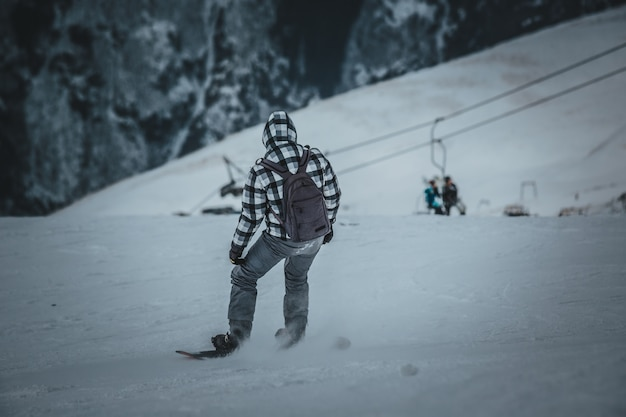 Snowboarder de homem passeios na encosta. estância de esqui.