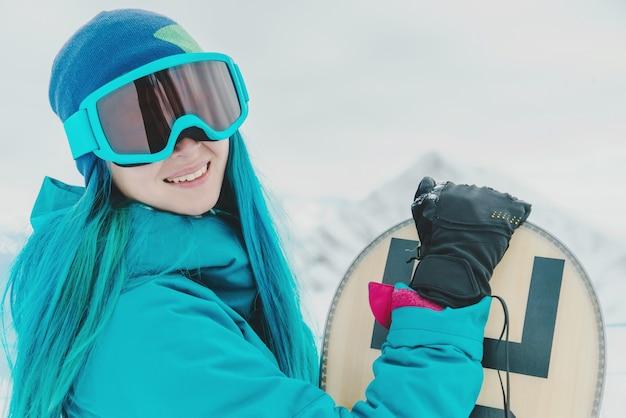 Snowboarder de mulher em óculos de sol protetores