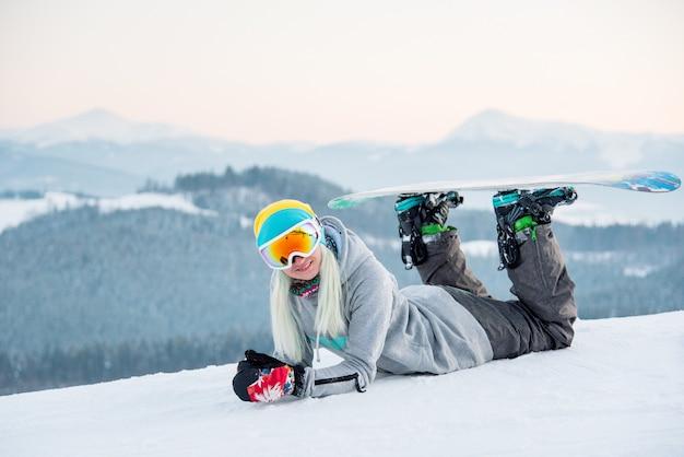Snowboarder de mulher relaxante ao ar livre, deitado na neve, sorrindo para a câmera
