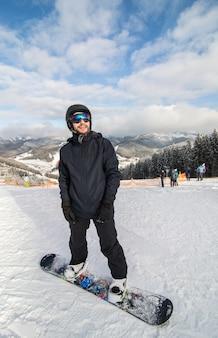 Snowboarder deslizando colina abaixo na pista de corrida na colina das montanhas