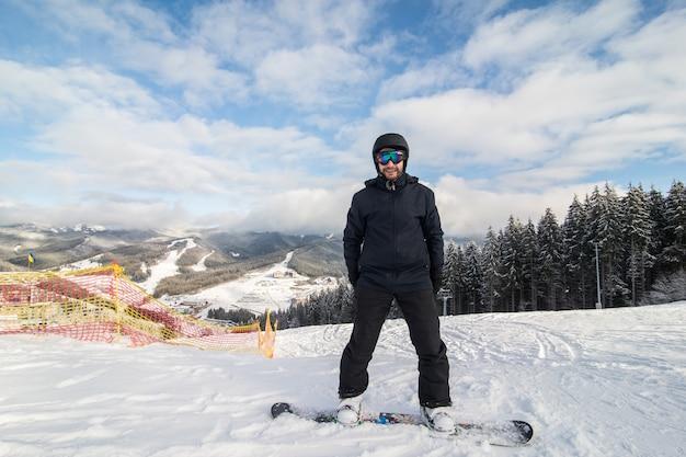 Snowboarder deslizando colina abaixo na pista de corrida na colina das montanhas Foto gratuita