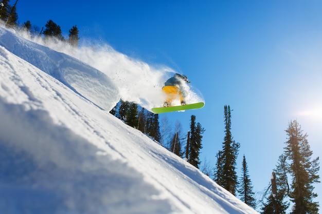 Snowboarder em montanhas inhigh do salto no dia ensolarado.