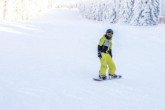 Snowboarder em movimento descendo a colina em um resort nas montanhas