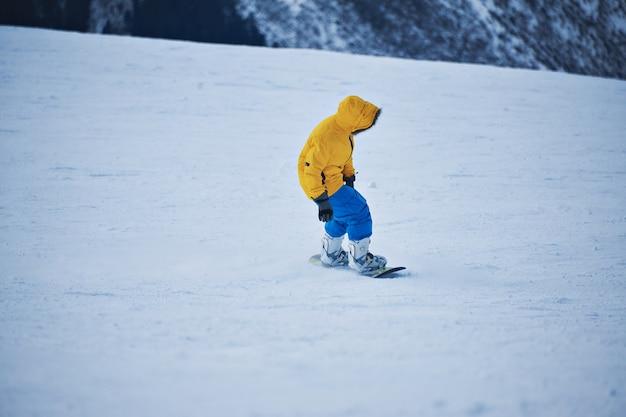Snowboarder em parka amarelo brilhante e calça azul olha para baixo na encosta de neve antes de começar a pedalar no dia ensolarado de inverno na estação de esqui na montanha