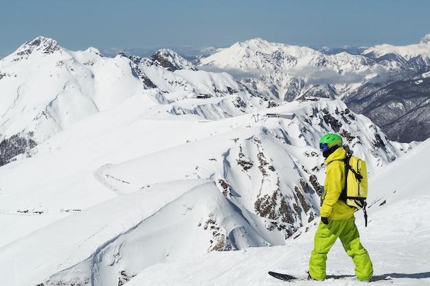 Snowboarder em pé no cume da montanha aibga do cáucaso, na rússia