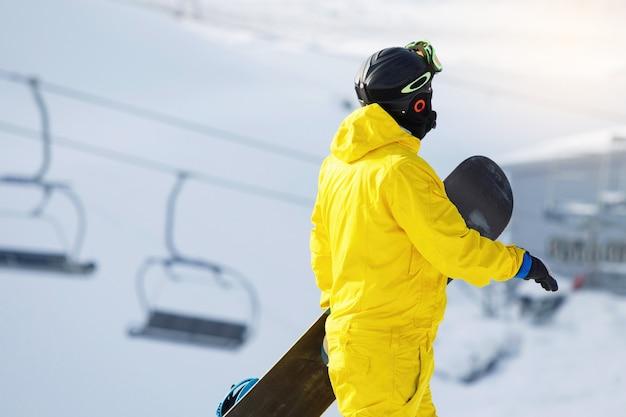 Snowboarder está caminhando em uma montanha coberta de neve. ele está usando uma máscara, capacete, óculos e um macacão amarelo
