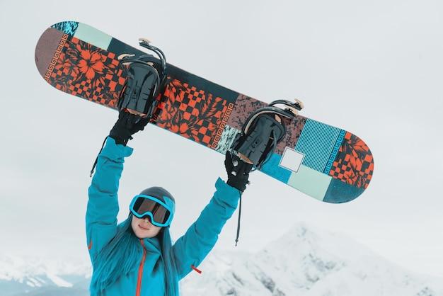 Snowboarder feliz da menina ao ar livre