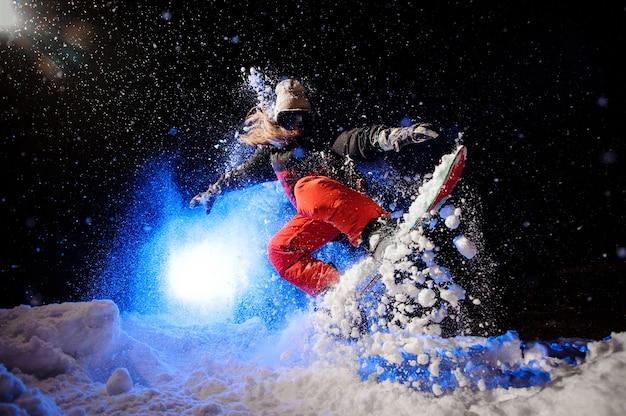 Snowboarder feminina vestida com uma roupa esportiva laranja, pulando na encosta da montanha à noite sob a luz azul
