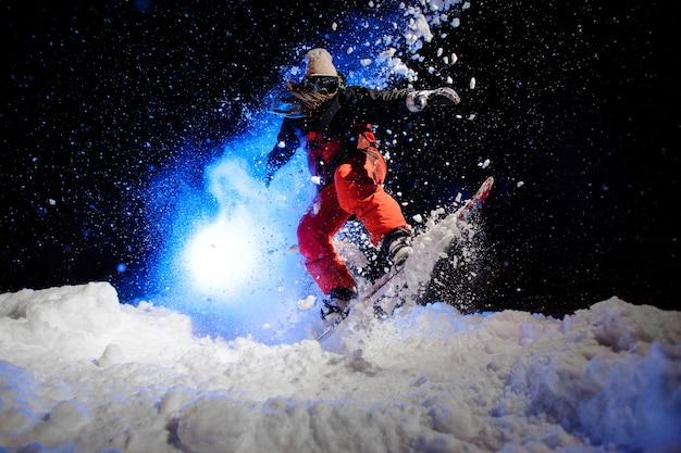 Snowboarder feminina vestida com uma roupa esportiva vermelha, pulando na encosta da montanha à noite sob a luz azul