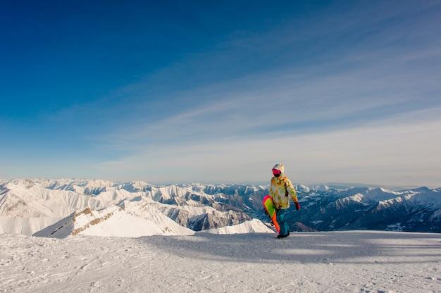 Snowboarder feminino em sportswear andando no pico da montanha