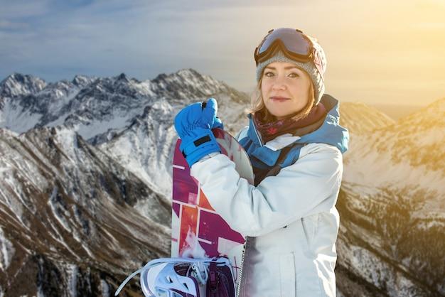 Snowboarder feminino, juntamente com snowboard entre as árvores
