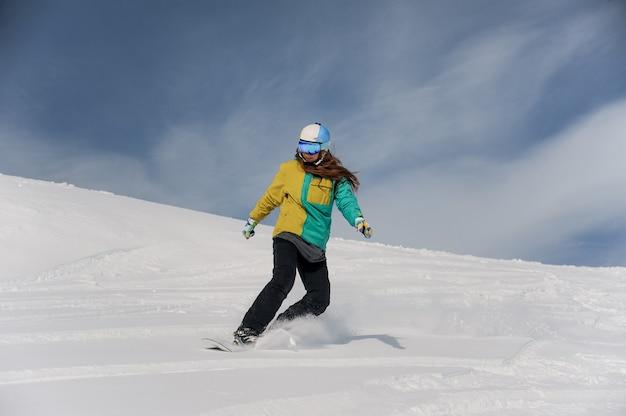 Snowboarder feminino no capacete e óculos descendo a encosta da montanha