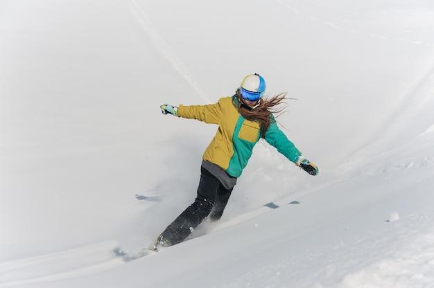 Snowboarder feminino no sportswear colorido e capacete descendo a colina de neve em pó