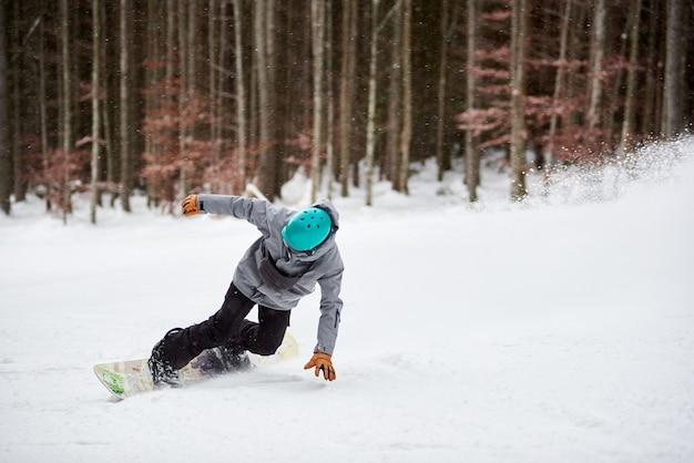 Snowboarder masculino com capacete azul, deslizando arriscado em uma estrada plana coberta de neve. troncos de árvores e floresta escura no fundo.