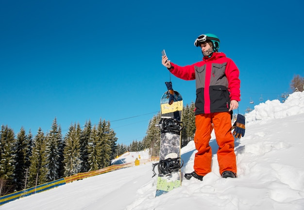 Snowboarder masculino descansando na encosta na estância de esqui, usando seu telefone inteligente após snowboard