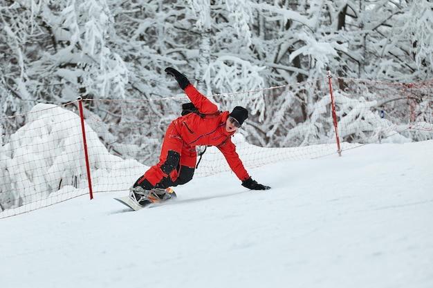 Snowboarder masculino em um terno vermelho anda na colina nevada com o conceito de snowboard, esqui e snowboard.