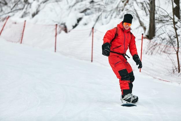 Snowboarder masculino em um terno vermelho cavalga na colina de neve com o conceito de snowboard, esqui e snowboard