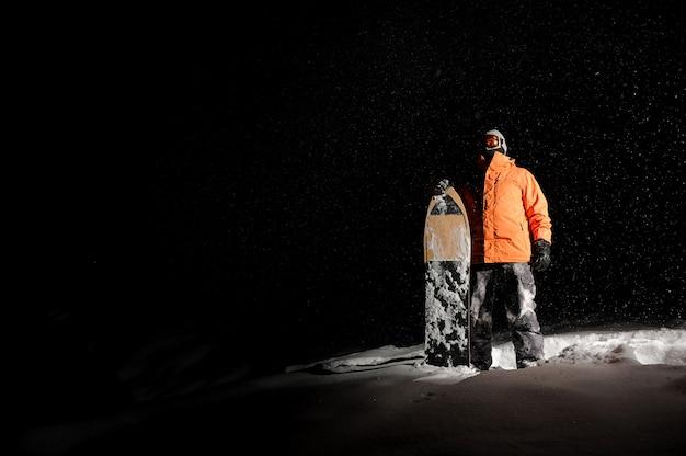 Snowboarder masculino no sportswear laranja em pé com a prancha na neve à noite