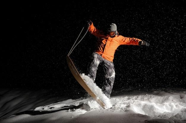 Snowboarder masculino no sportswear laranja, equilibrando na neve à noite