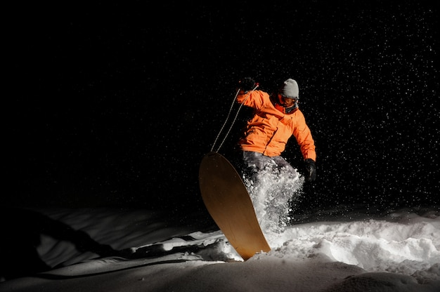 Snowboarder masculino no sportswear laranja, equilibrando-se no snowboard à noite