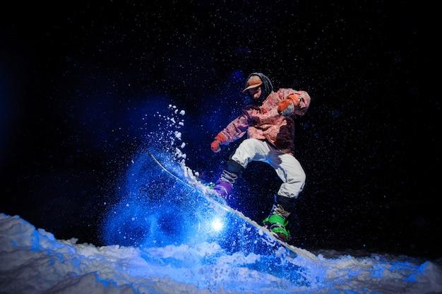 Snowboarder masculino, vestido com um sportswear branco e rosa realiza truques na encosta da neve