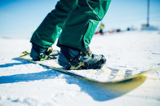 Snowboarder montando uma colina de neve, esporte radical