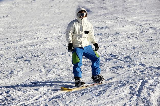 Snowboarder pequeno no contexto do céu azul.