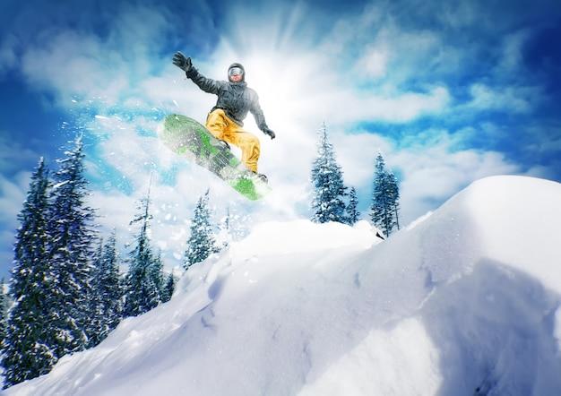 Snowboarder salta contra o céu e as árvores