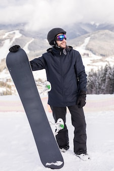 Snowboarder segurar snowboard no topo da colina perto do retrato, montanhas de neve snowboard nas encostas.