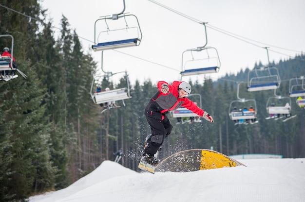 Snowboarder voando para baixo de um obstáculo no dia de inverno