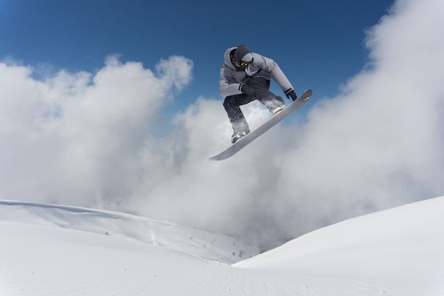 Snowboarder voando sobre montanhas.