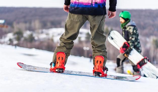 Snowboarders em pista em montanhas nevadas