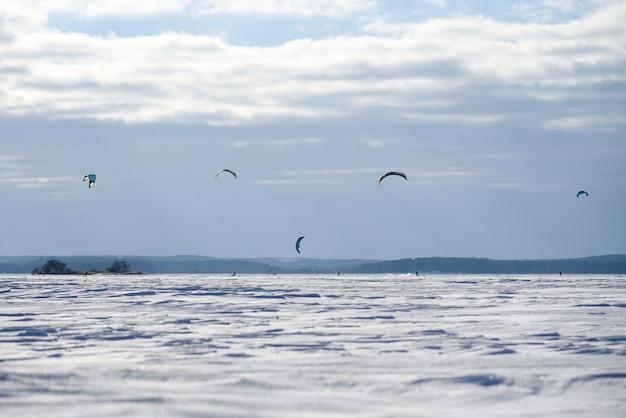 Snowboarders no passeio de pára-quedas no lago congelado.