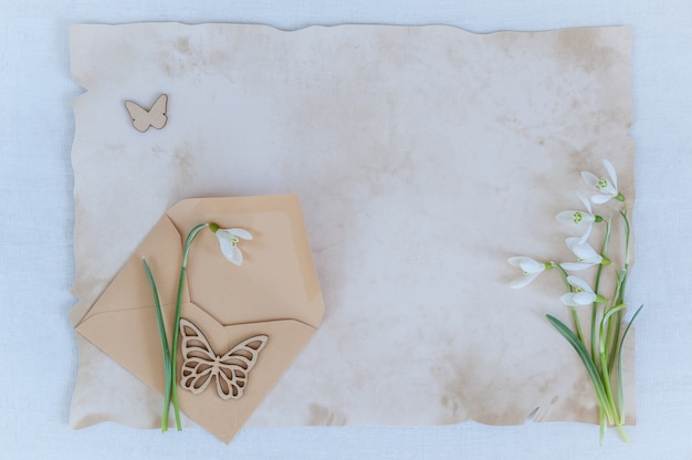 Snowdrops com envelope e papel para texto em um fundo de madeira