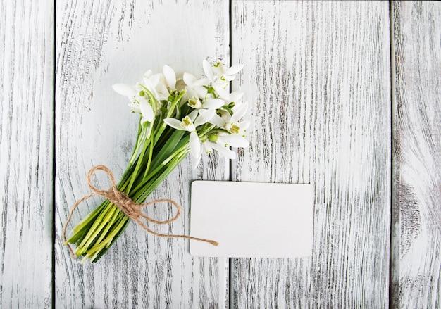 Snowdrops flores com cartão em uma mesa de madeira