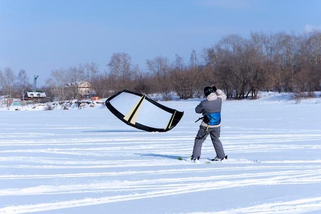 Snowkiter pega o vento com sua pipa, parado no gelo de um lago congelado contra a costa