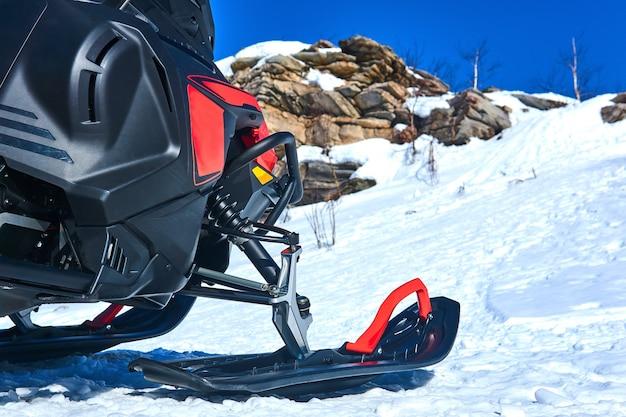 Snowmobile em primeiro plano contra uma paisagem montanhosa desfocada de inverno