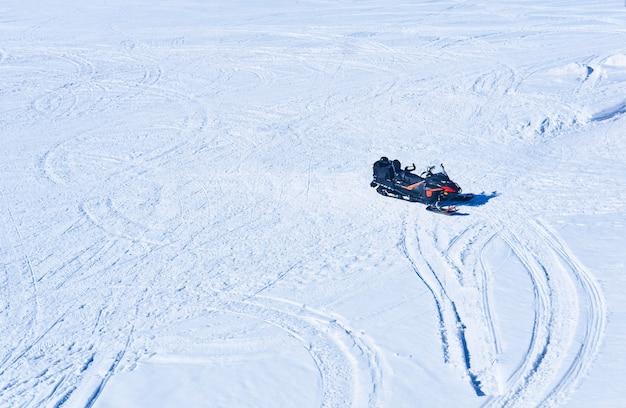 Snowmobile em um campo nevado com vestígios de muitas máquinas de neve, vista superior