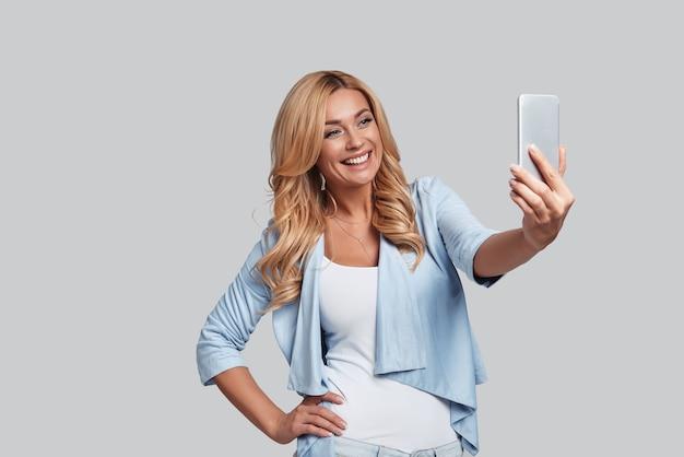 Só mais um tiro. mulher jovem e atraente tirando uma selfie e sorrindo em pé contra um fundo cinza