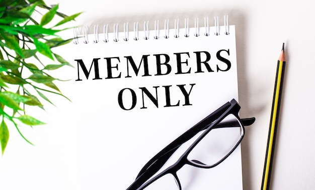 Só membros está escrito em um caderno branco ao lado de um lápis, óculos de armação preta e uma planta verde