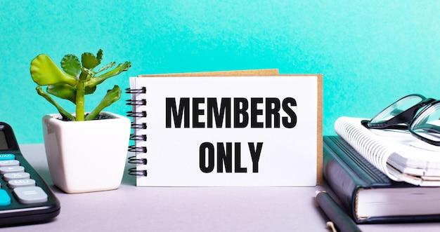 Só membros está escrito em um cartão branco ao lado de um vaso de flores, diários e calculadora